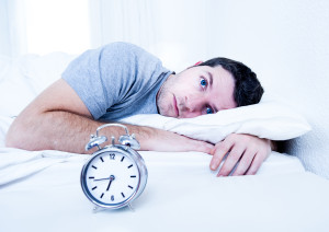 man in bed with eyes opened suffering insomnia disorder